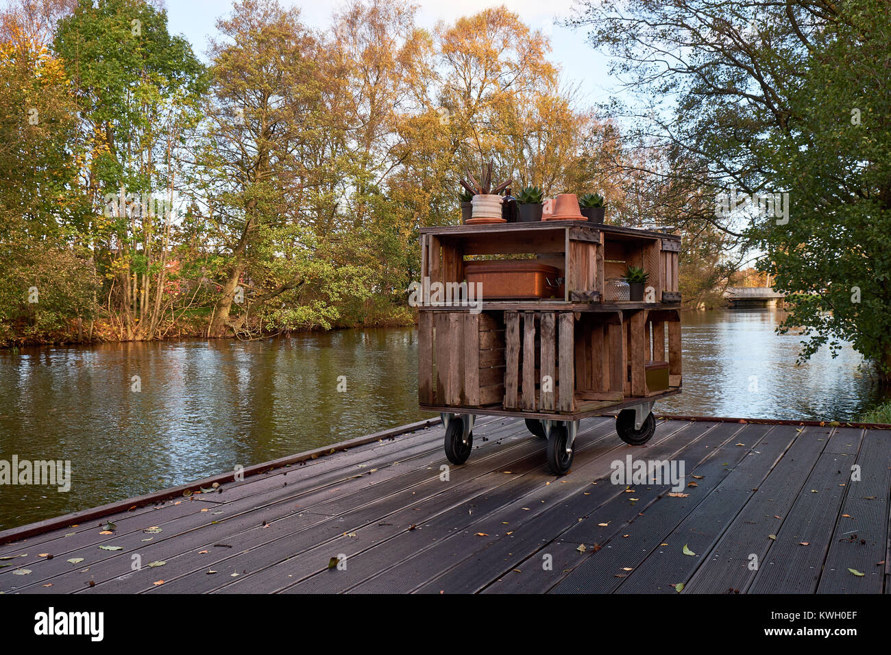 Home made storage furniture of wood boxes standing on a wooden jetty by a river - Stock Image