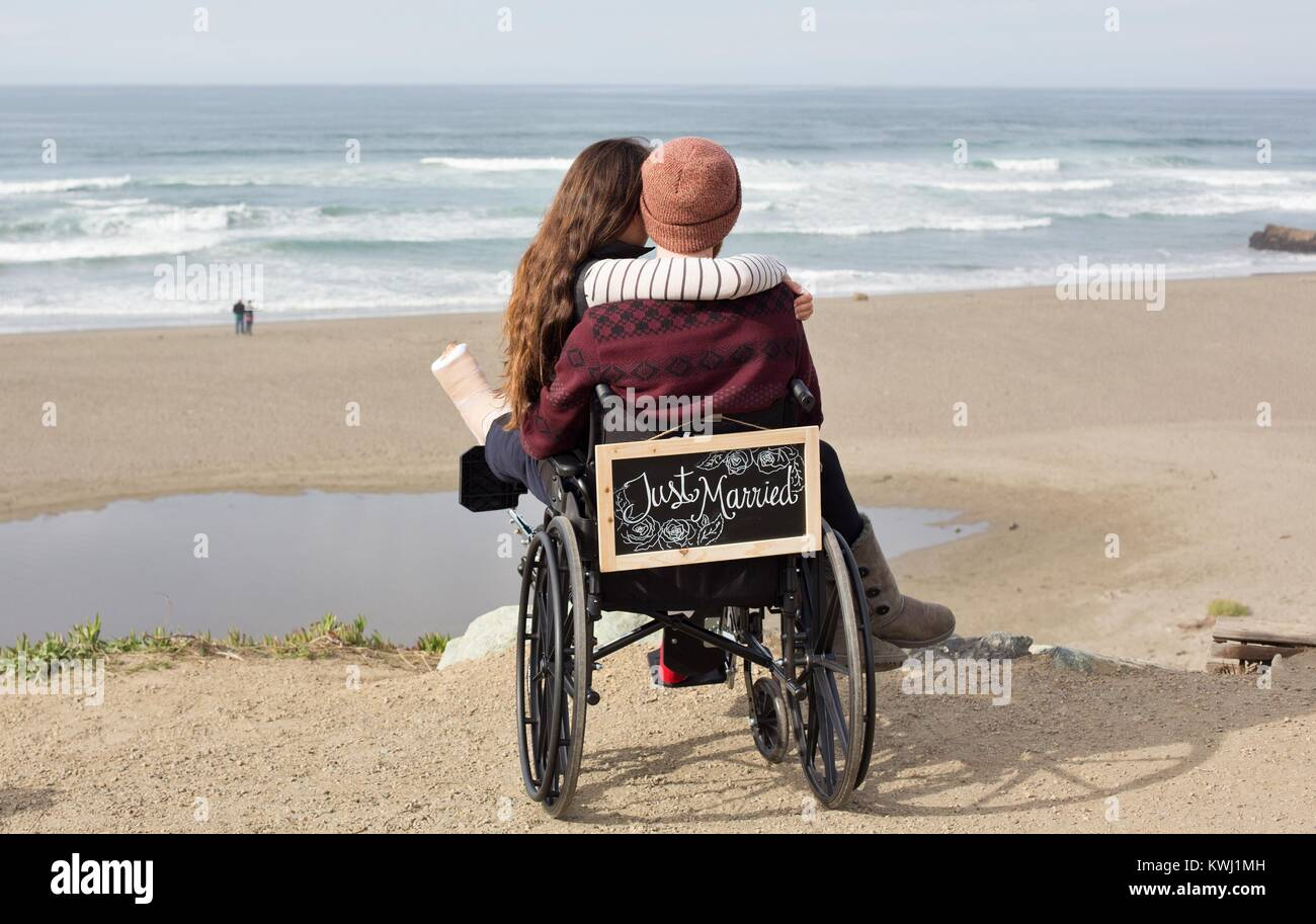 A man in a wheelchair holds his bride on his lap on their honeymoon, at Salmon Creek Beach in Bodega Bay, California, - Stock Image