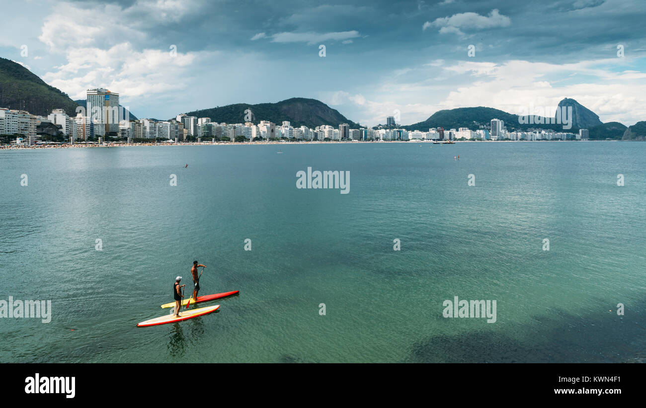 two-men-on-a-stand-up-paddle-on-copacabana-beach-rio-de-janeiro-brazil-KWN4F1.jpg