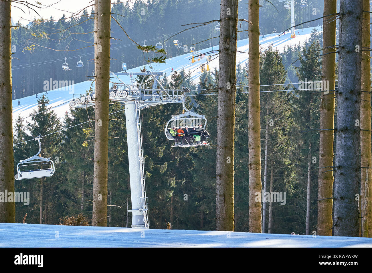 WINTERBERG, GERMANY - FEBRUARY 15, 2017: Chairlift going through a pine tree forest at Ski Carousel Winterberg - Stock Image