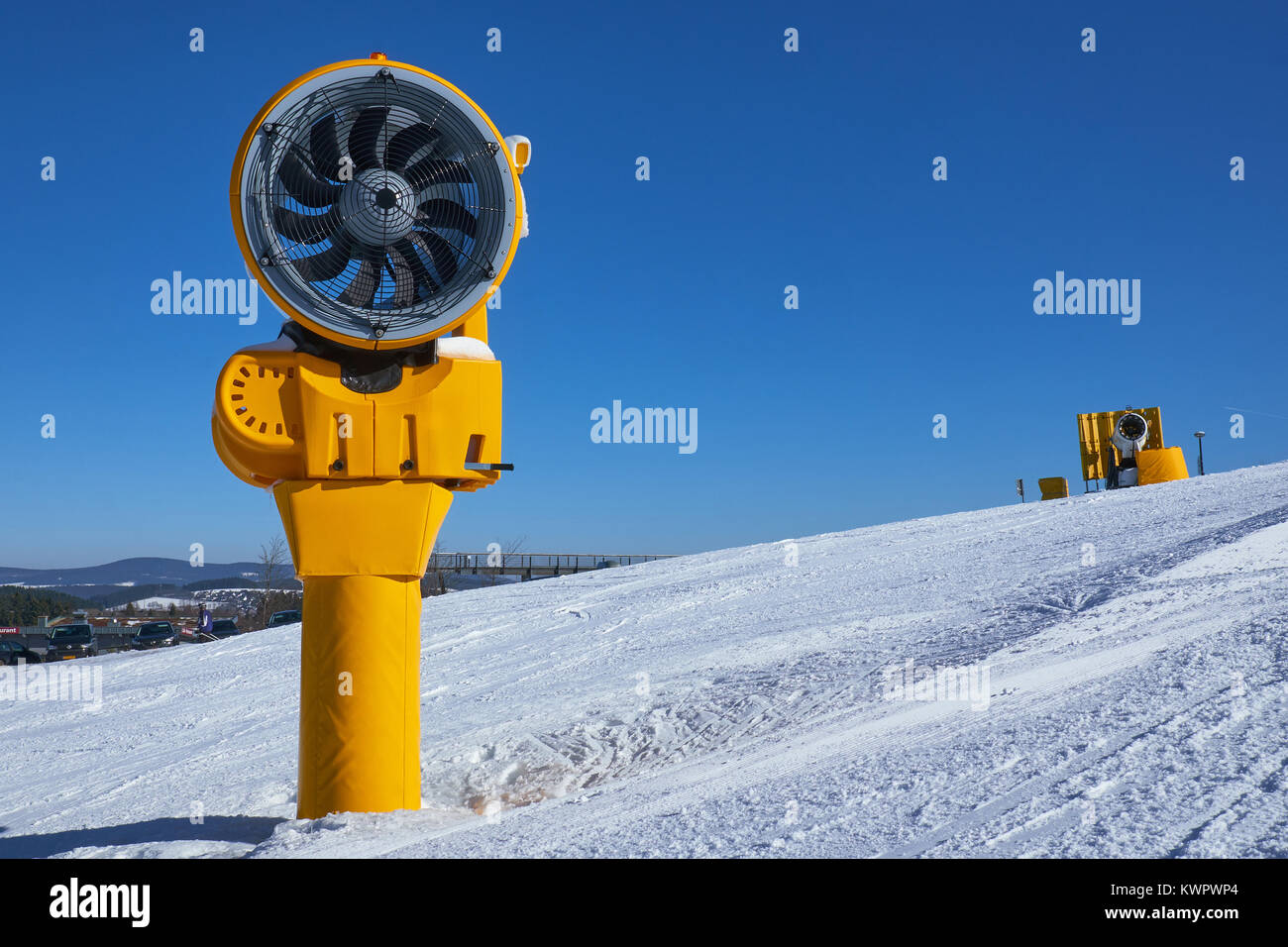 Two turned off yellow snow cannons on a piste at Ski Carousel Winterberg against a clear blue sky - Stock Image