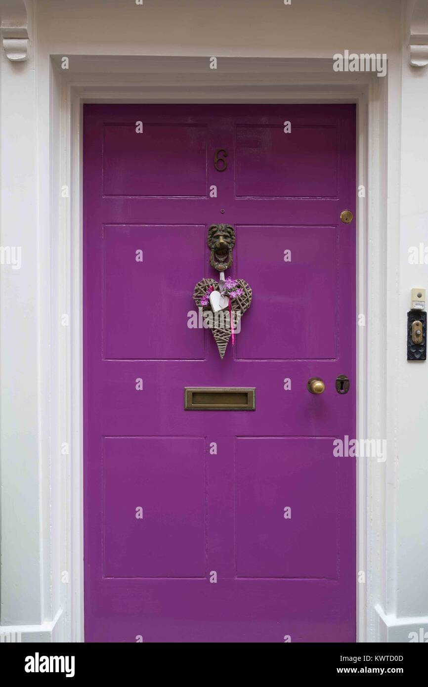 Vivid purple front door main entrance to a town house. - Stock Image