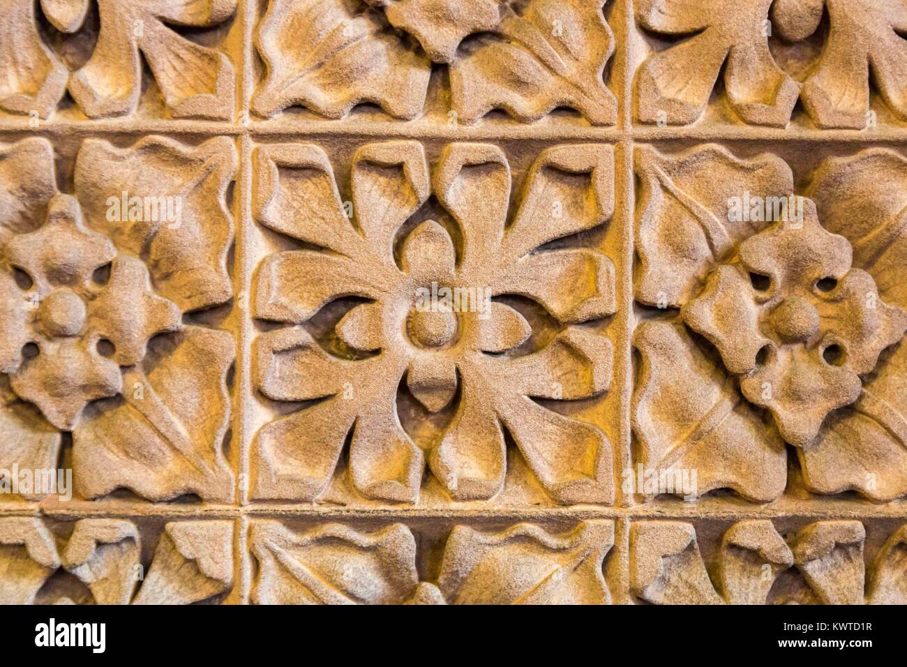 Wall or screen of carved stone depicting flower motif patterns - Stock Image