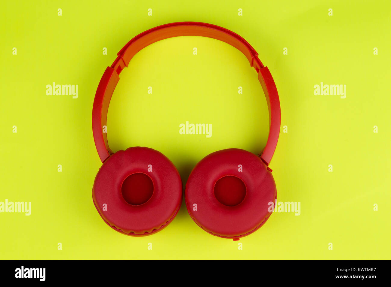 A colorful top view of a tangerine red headphones - Stock Image