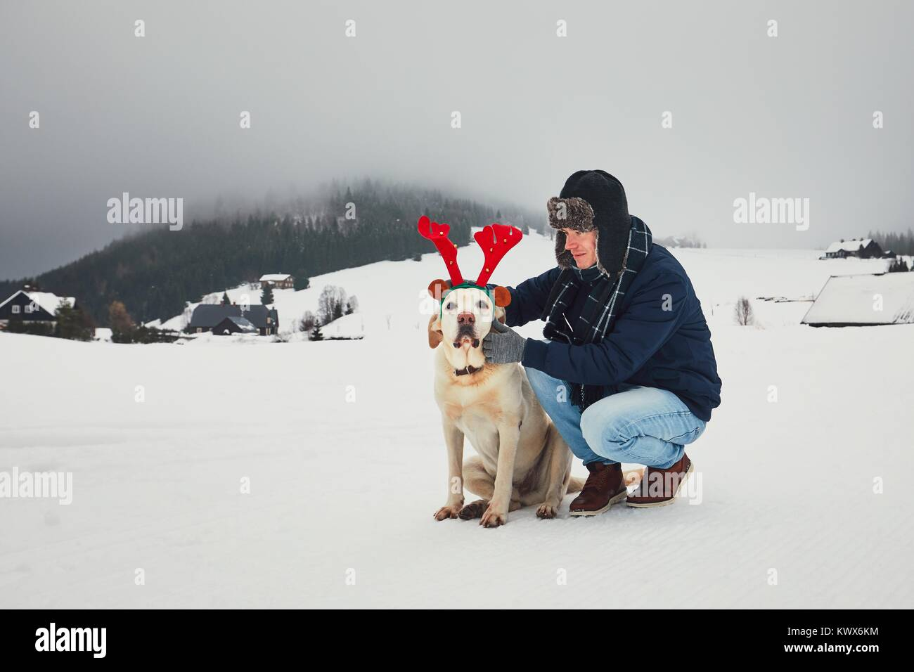 Funny walk with dog in the snowy landscape. Labrador retriever is wearing fake reindeer antlers. Winter season in - Stock Image