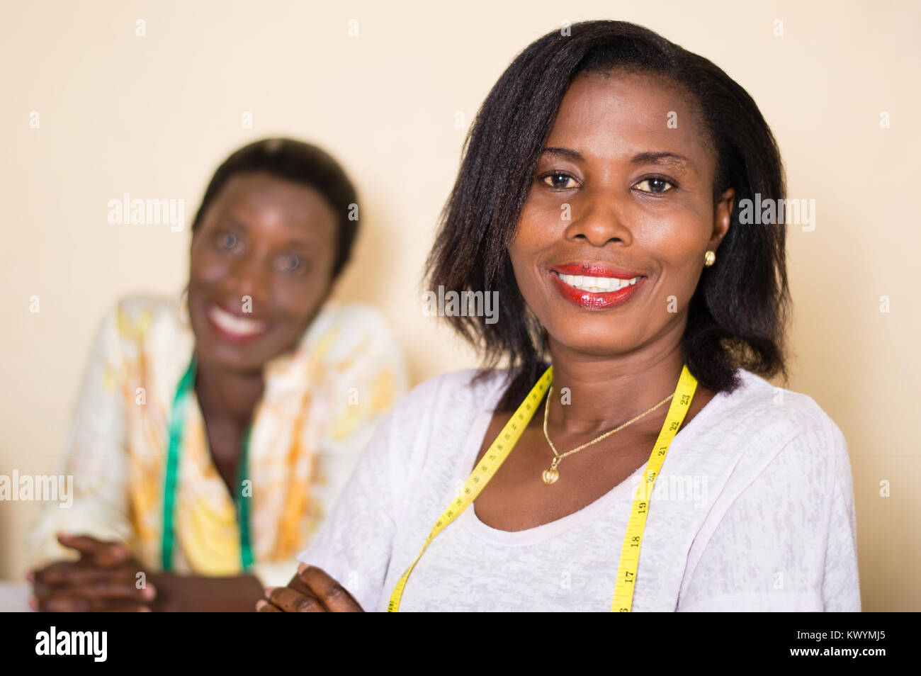 Smiling seamstress in her workshop looks at the camera with her colleague in the background. - Stock Image