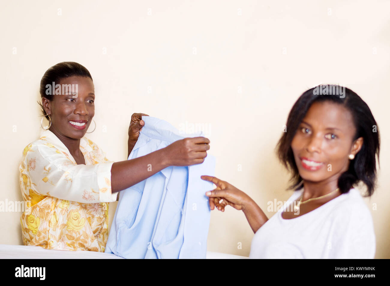 Teacher in sewing holds in her  hands a shirt that shows her  trainee. - Stock Image
