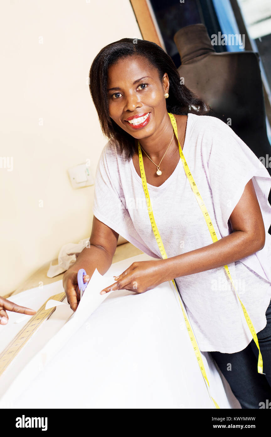 the student  seamstress learns  cutting  fabric for making clothes. - Stock Image