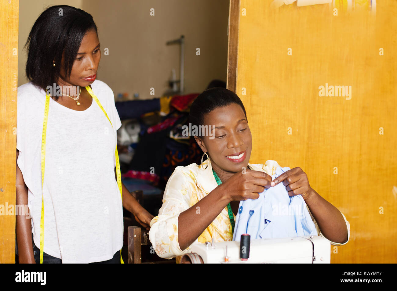 professional seamstress sews and student notes. - Stock Image