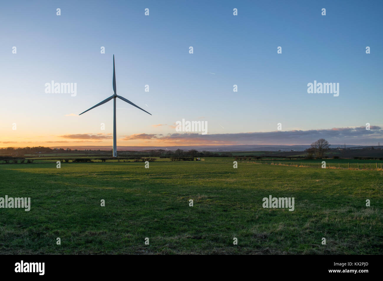 Wind Turbine in front of a Sunset - Stock Image