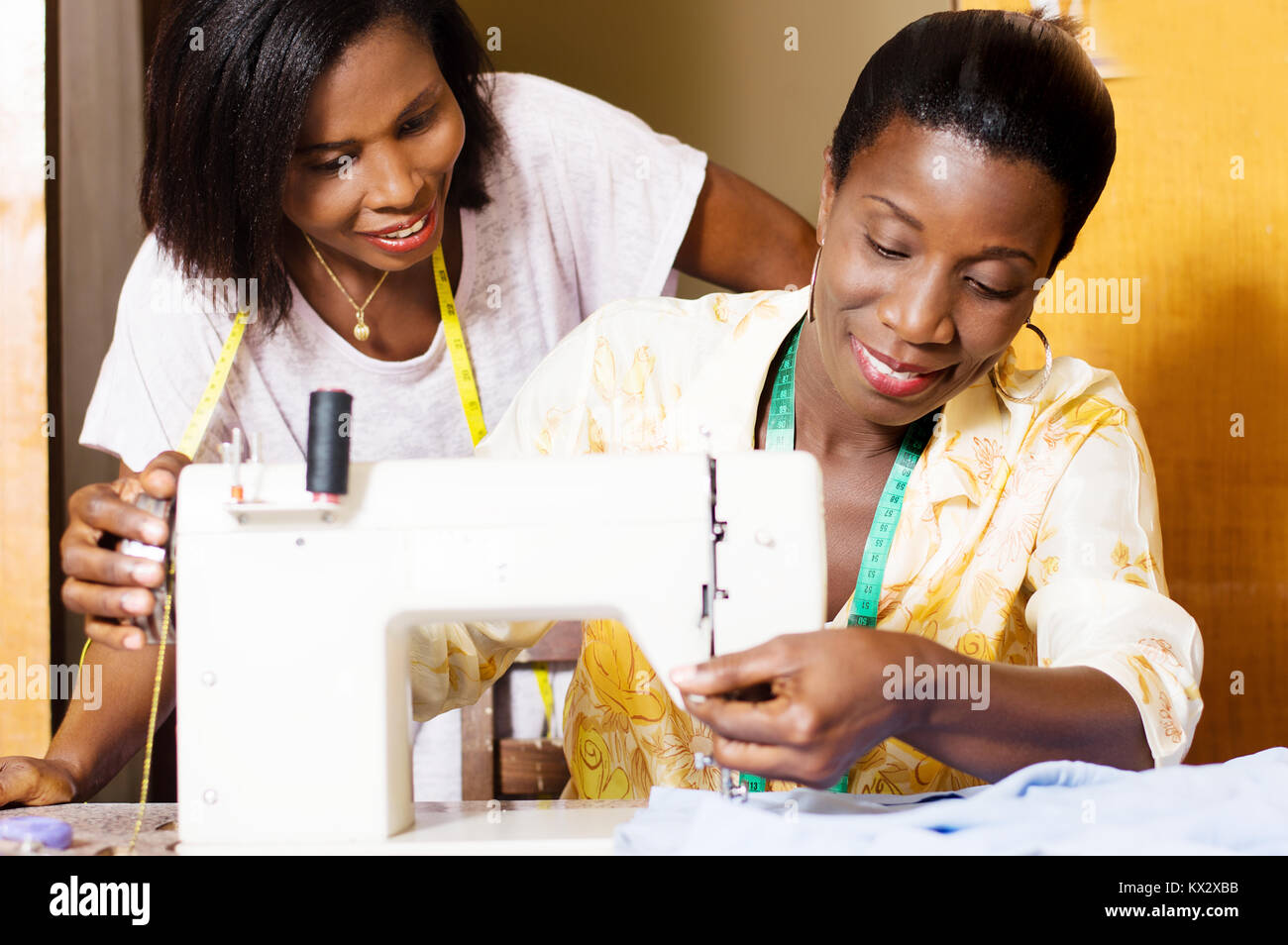 The professional seamstress sews and his trainee assists from behind. - Stock Image