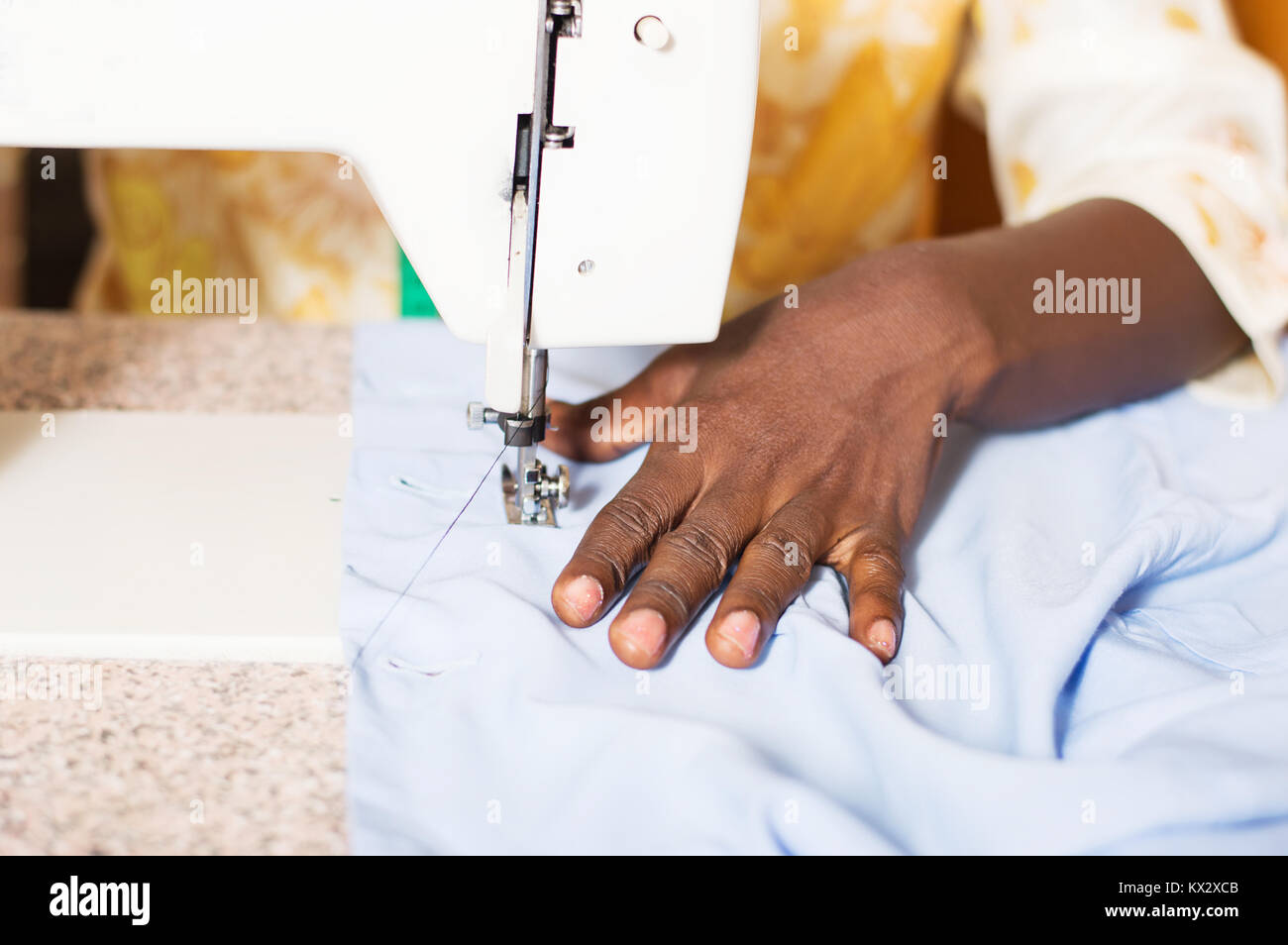 closeup of the woman's hand behind a sewing machine. - Stock Image