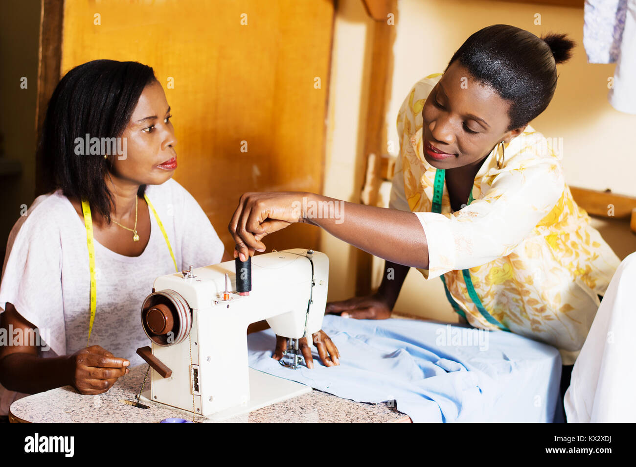 professional seamstress helps his student in practice. - Stock Image