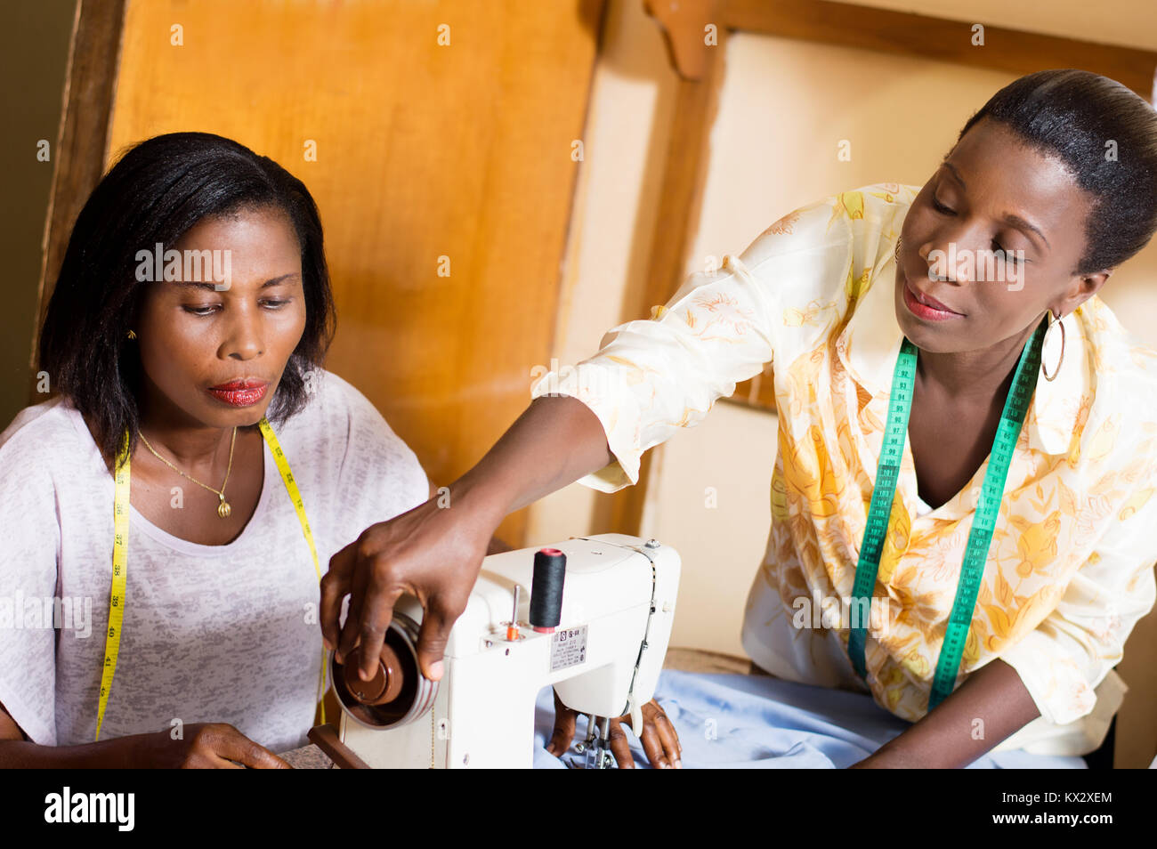 seamstress assists its students to the mastery of her sewing machine - Stock Image