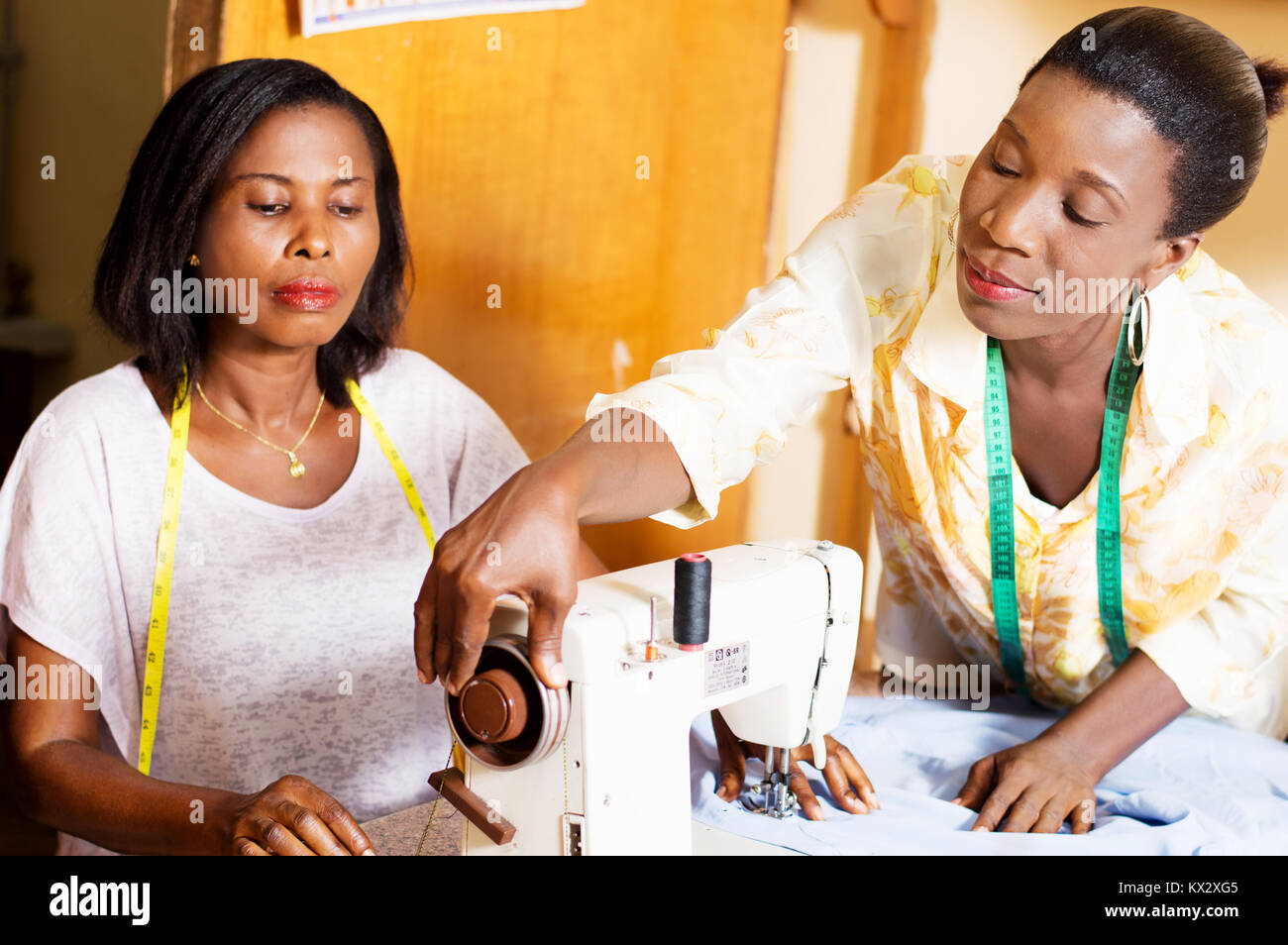 seamstress assists its students to the mastery of her sewing machine. - Stock Image