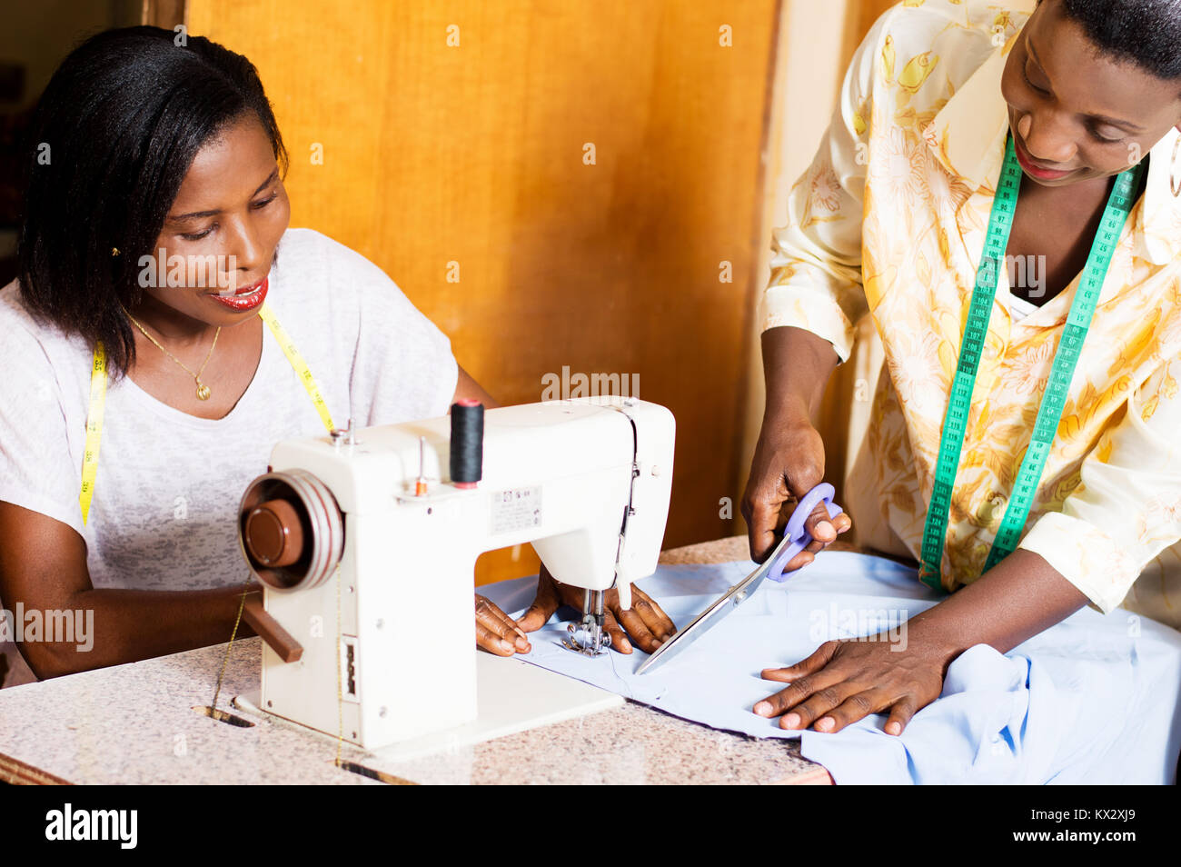 the seamstress cut the cloth to her  intern. - Stock Image
