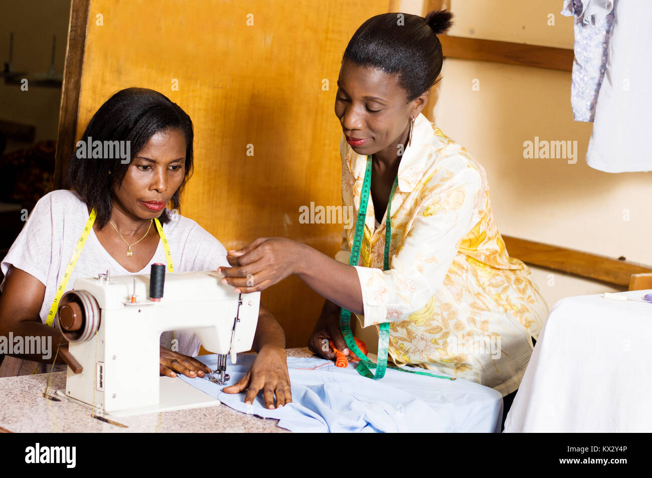 Seamstress straighten the wire machine of her  student - Stock Image
