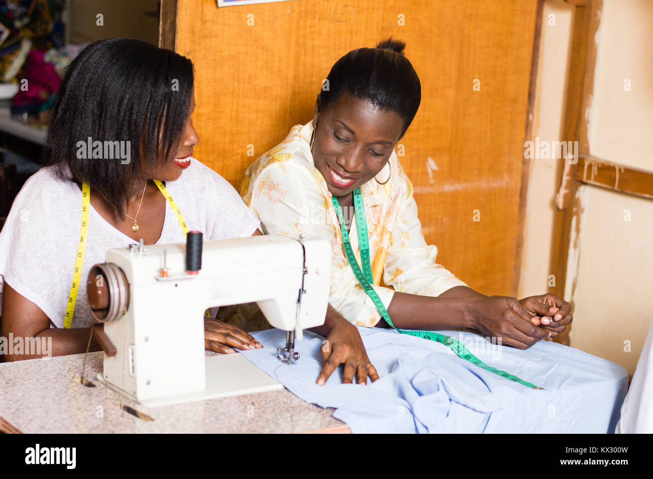 the student is happy to learn sewing and pleases her  teacher. - Stock Image