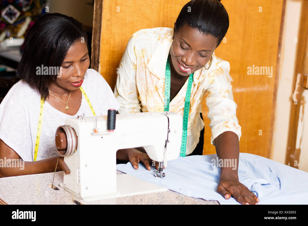 seamstress teaches her  students how to put a shirt under the needle of a sewing machine. - Stock Image