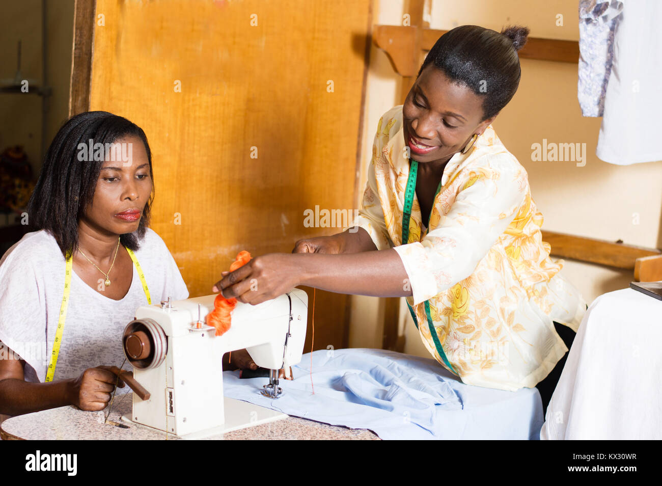 Sewing teacher shows her student how to place a roll of yarn on a sewing machine - Stock Image