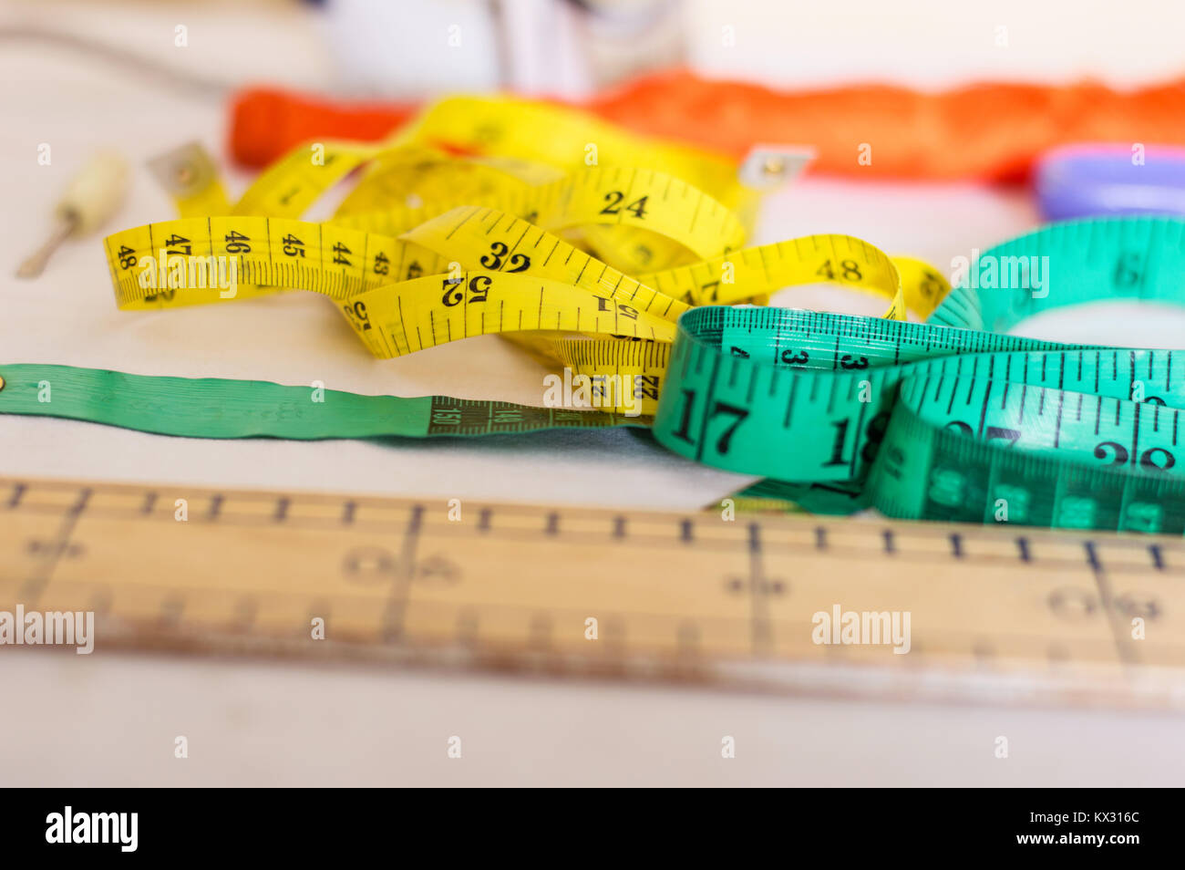 Ribbon meters, a screwdriver and a ruler arranged on a table in a sewing workshop. - Stock Image