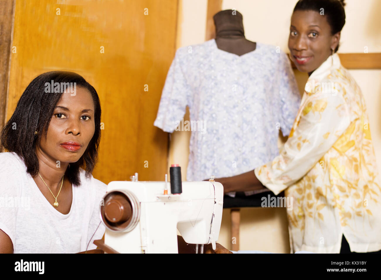 Young seamstress in front of her sewing machine while her colleague dresses the mannequin. - Stock Image