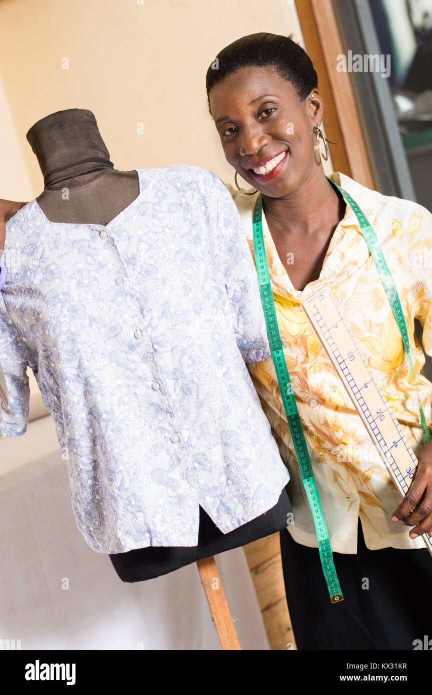 Young smiling seamstress stands next to her mannequin and looks at the camera. - Stock Image