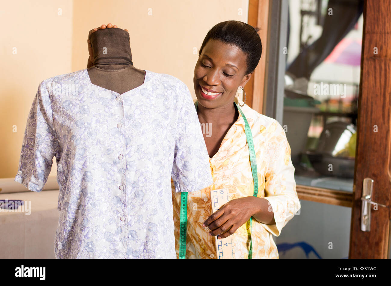 Young seamstress smiling satisfied with her work, admires her mannequin. - Stock Image