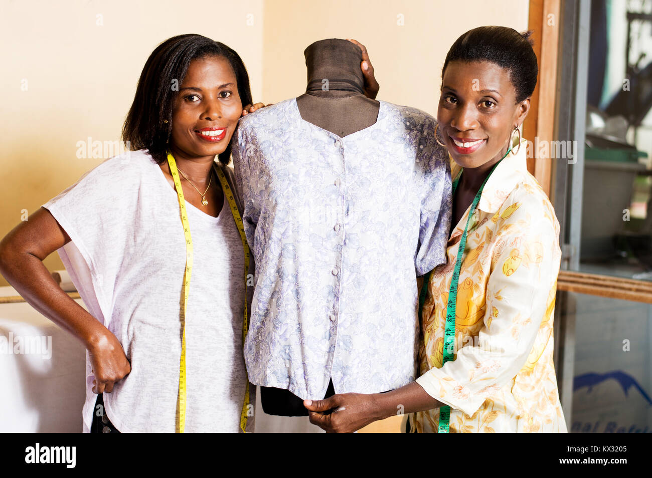 Two smiling seamstresses standing next to a mannequin in their studio. - Stock Image