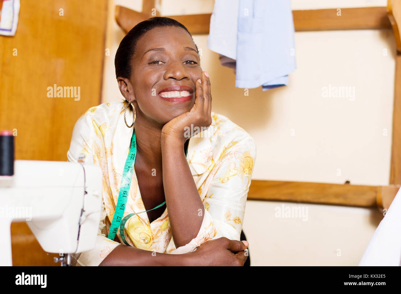 Beautiful woman seamstress smiling leaning on the table of her sewing machine and hand under the chin. - Stock Image