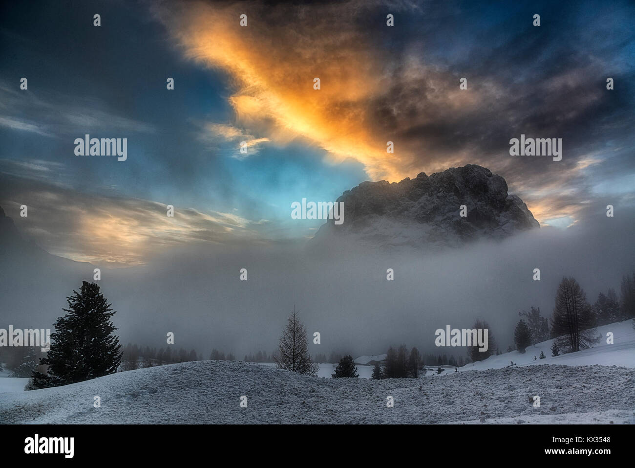 misty hills and sunset over the dolomites mountains in a cold winter with clouds in the blue sky - Stock Image