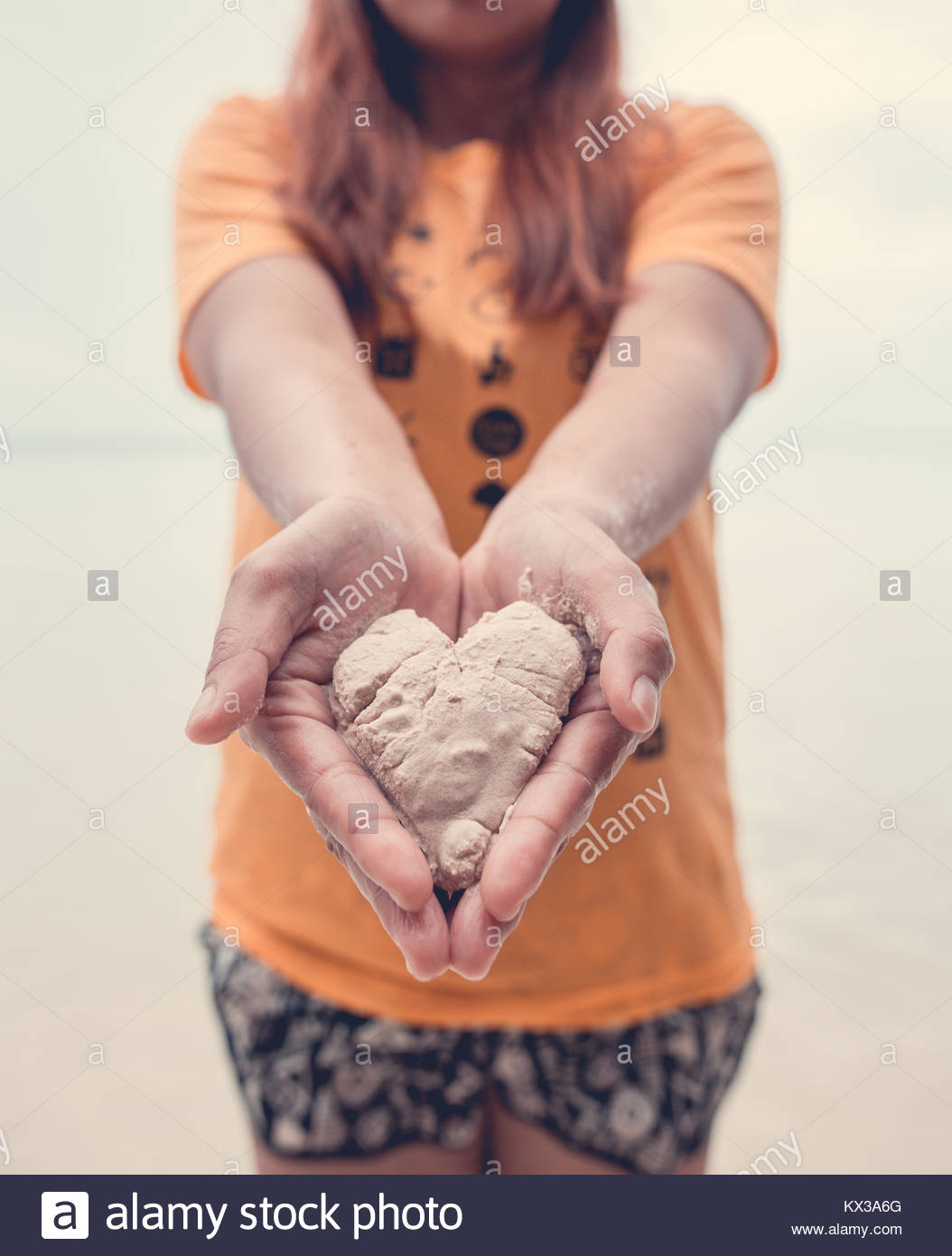 Girl holding sand in the shape of a heart, on a shore in the Philippines - Stock Image