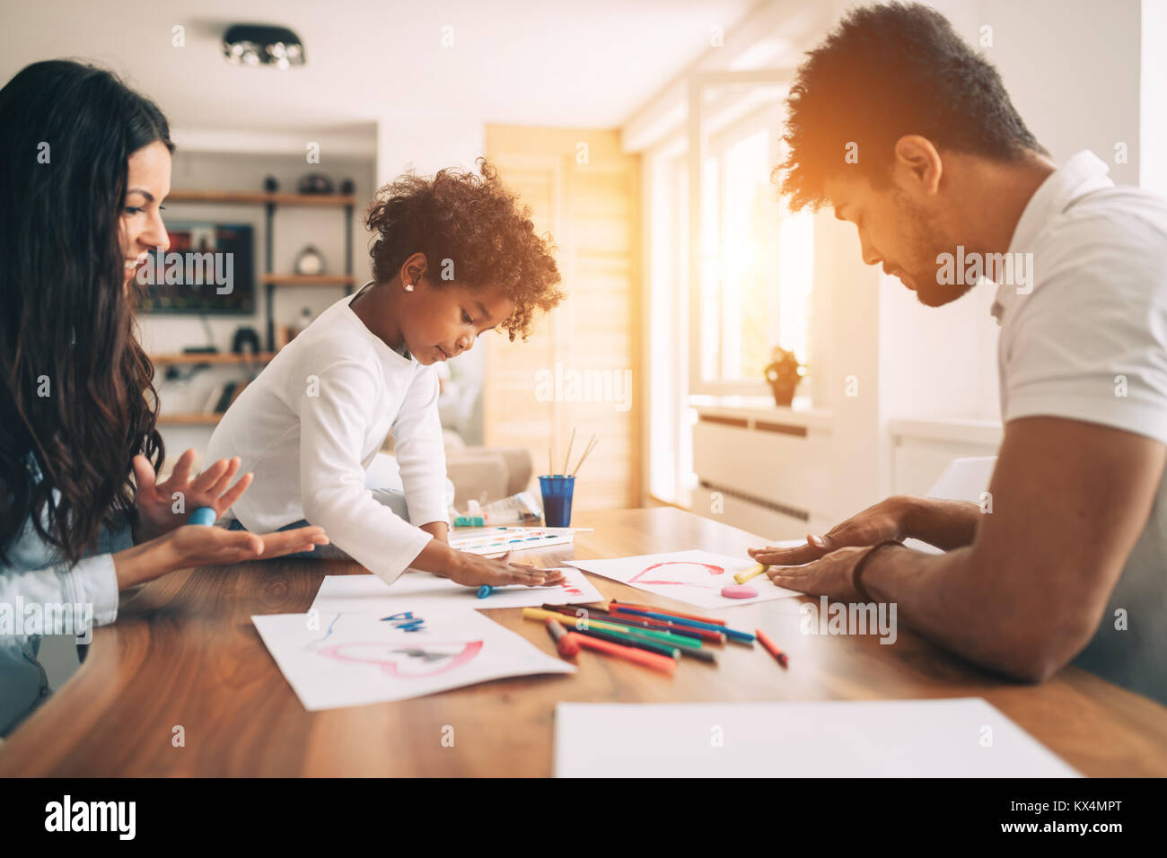 Happy young family relax and have fun at home - Stock Image