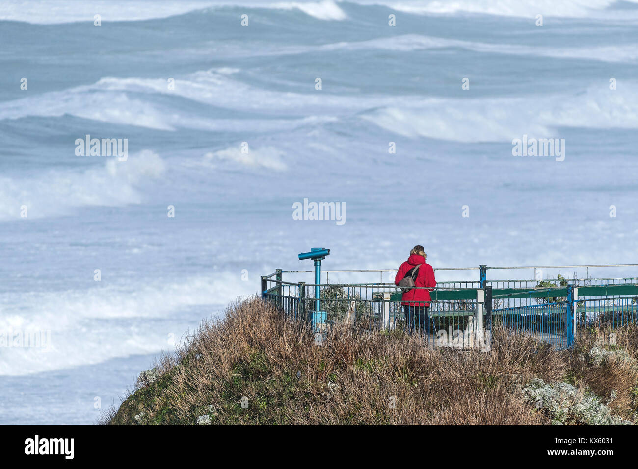 A man wearing a red jacket standing on a viewing platform overlooking the sea in Newquay Cornwall - Stock Image
