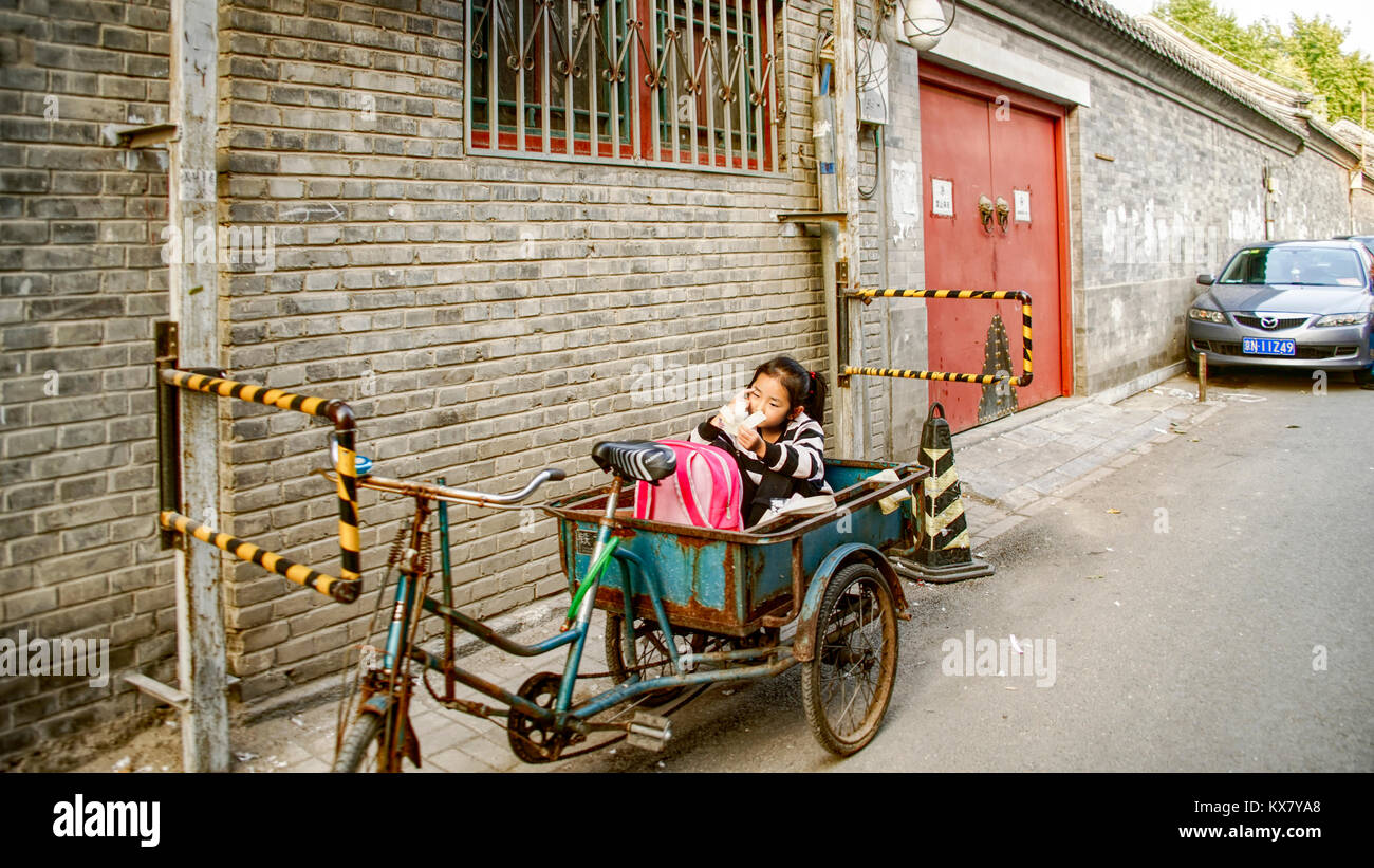 A young girl sits in a bicycle cart in the reserved parking spot at her residence. Traditional houton area.  Beijing, - Stock Image