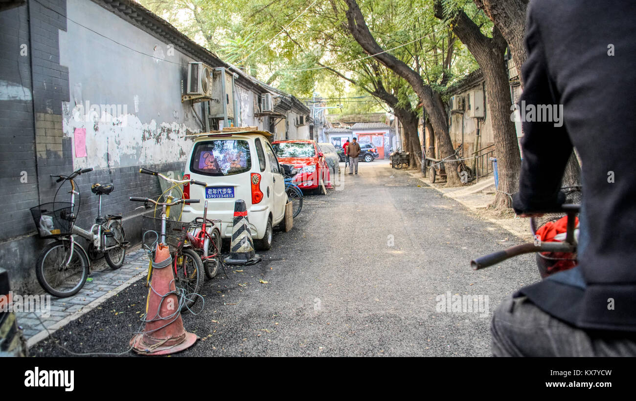 An alleyway in a traditional Chinese houton area with cars, bicycles and people. Beijing, China - Stock Image