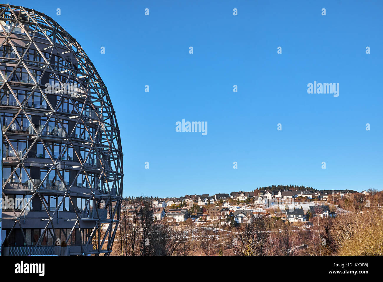 WINTERBERG, GERMANY - FEBRUARY 14, 2017: Futuristic egg shaped framework hotel building in front of small villas - Stock Image