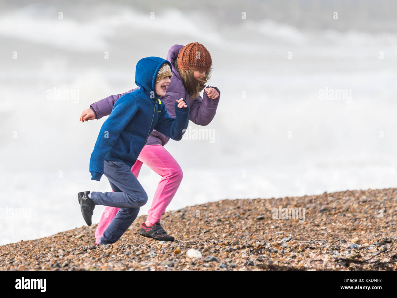 young-children-on-a-shingle-beach-in-winter-wrapped-up-in-coast-and-KXDNF8.jpg
