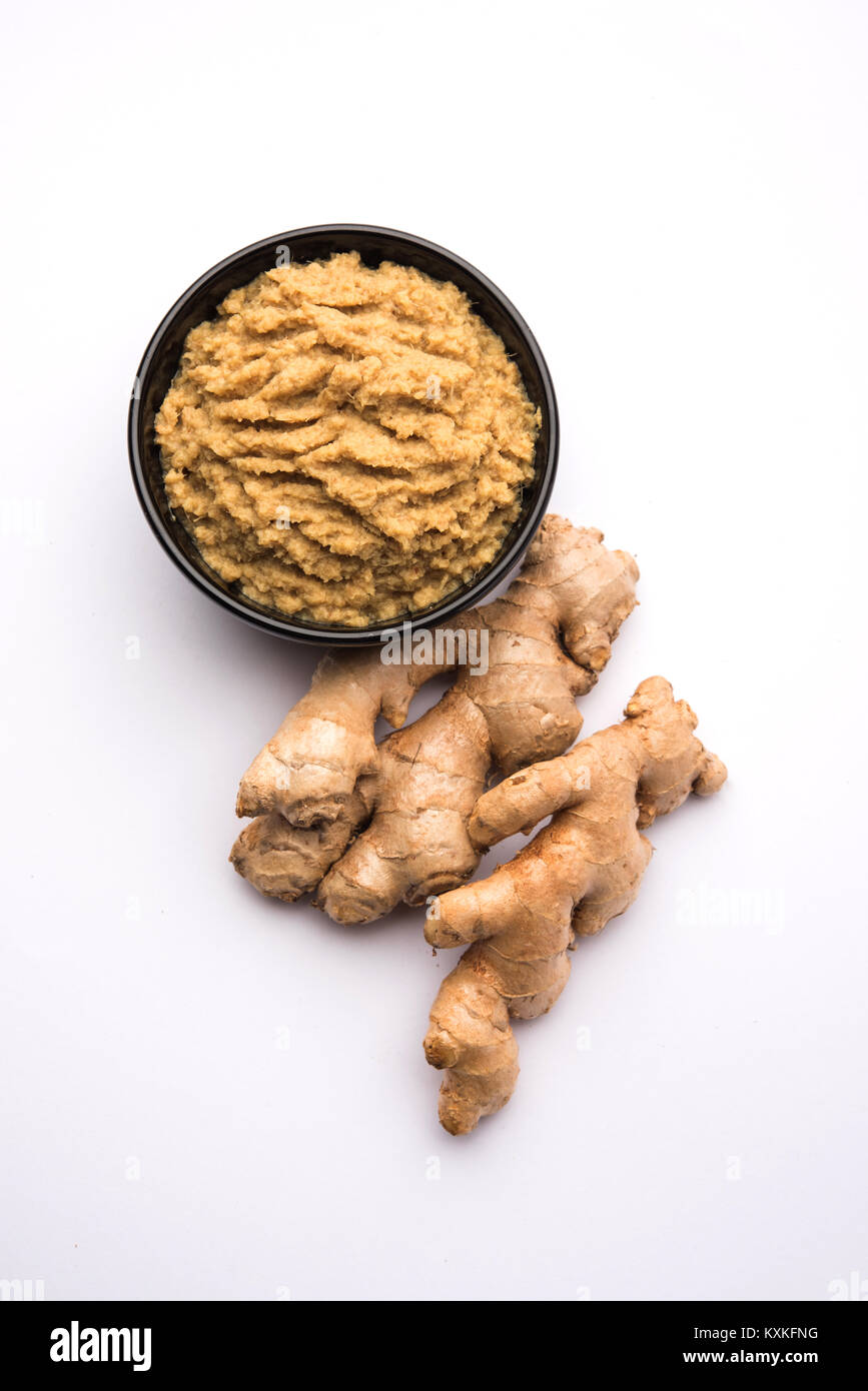 Fresh mashed Ginger / Ginger paste in white bowl with raw ginger over white background - Stock Image