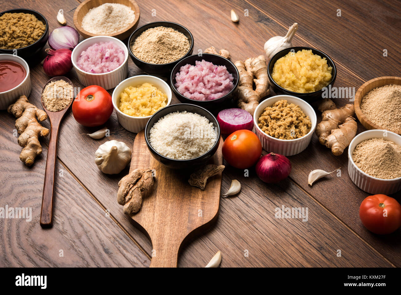 Ginger, Garlic, onion and tomato paste and powder in and raw form. Group of Basic Indian food ingredients over wooden - Stock Image