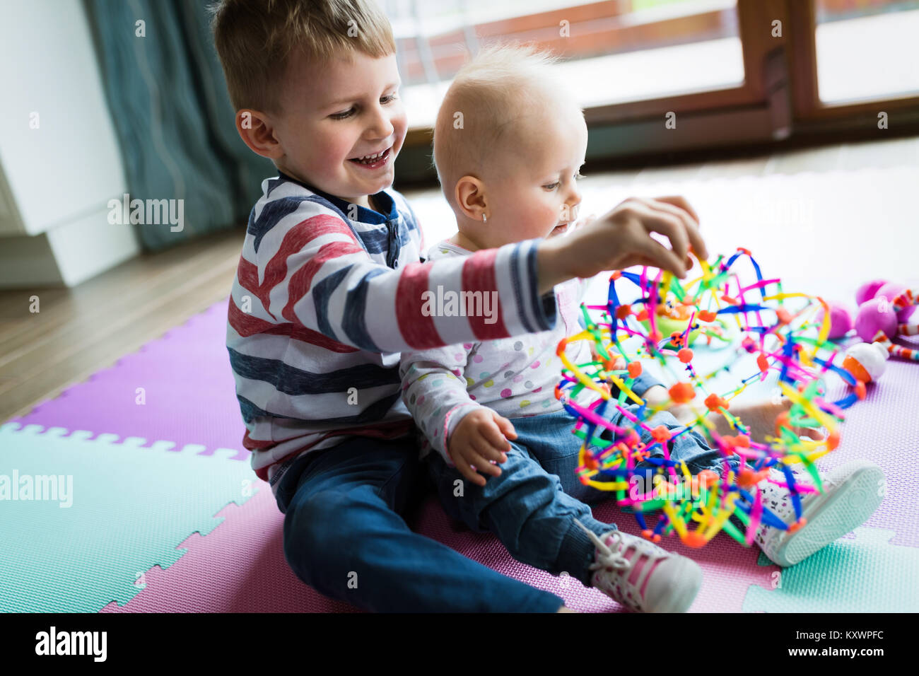 Cute little children playing while sitting on carpet - Stock Image