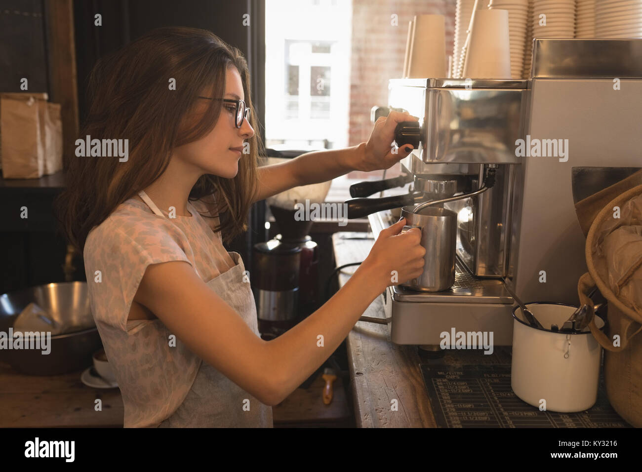 Barista steaming milk at the coffee machine - Stock Image