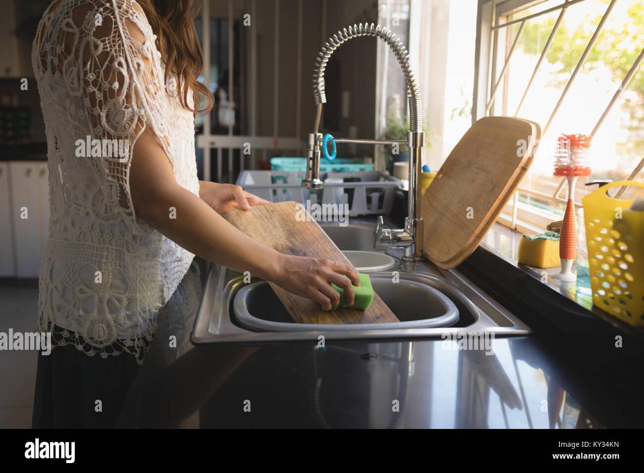 Woman washing cutting board in sink - Stock Image