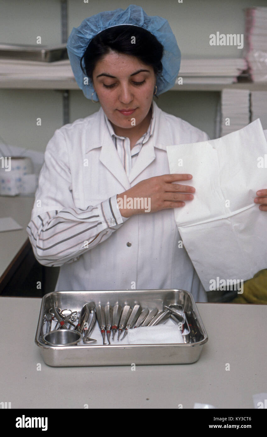 woman hospital worker sterilising surgery equipment - Stock Image