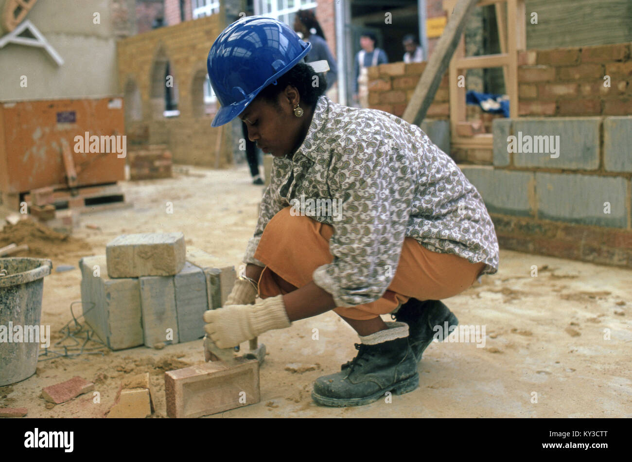 Woman learning to be a brick builder - Stock Image