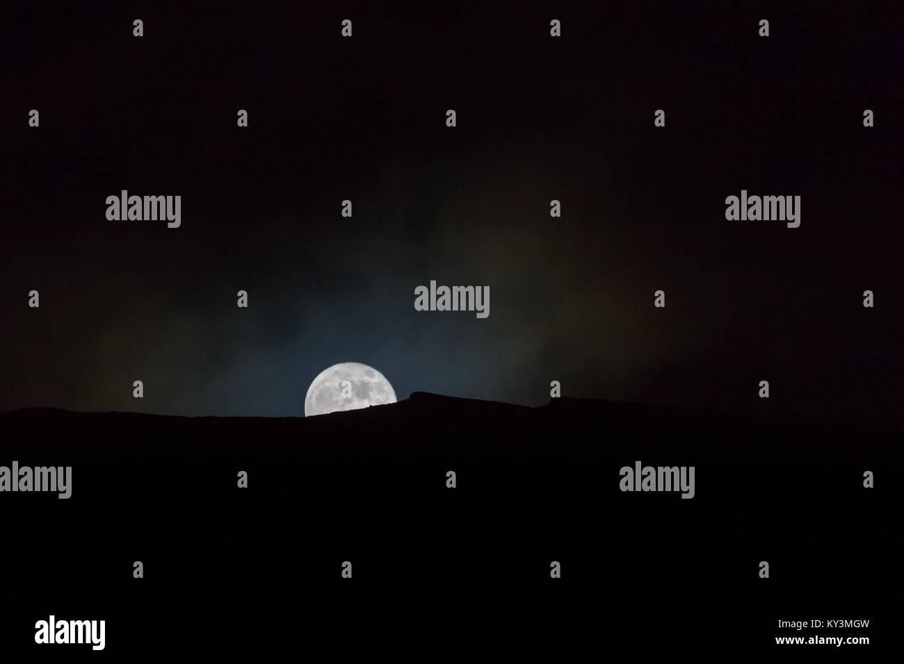 Full moon rising over a silhouetted ridge on a mountain with light mist and lunar craters visible - Stock Image