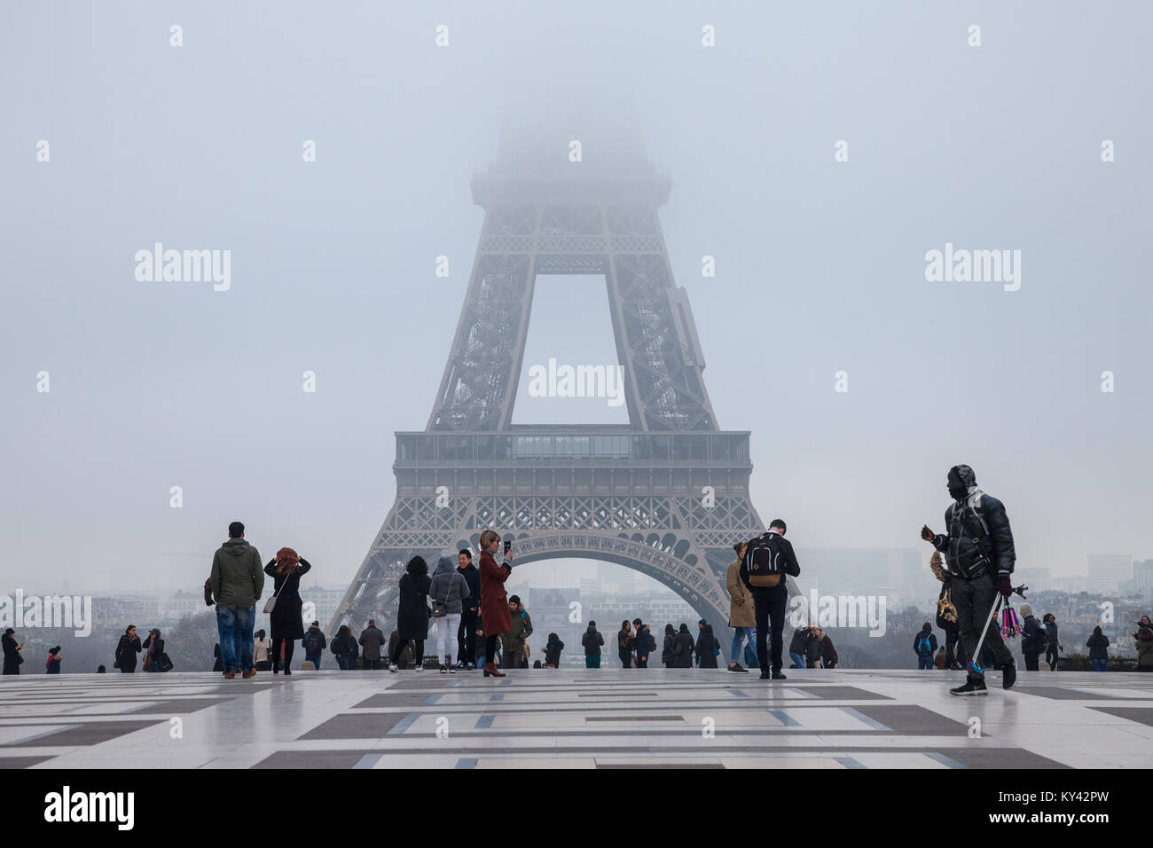 PARIS, FRANCE - DECEMBER 19, 2017: Tourists taking pictures in front of the Eiffel Tower, the top of the tower hidden - Stock Image