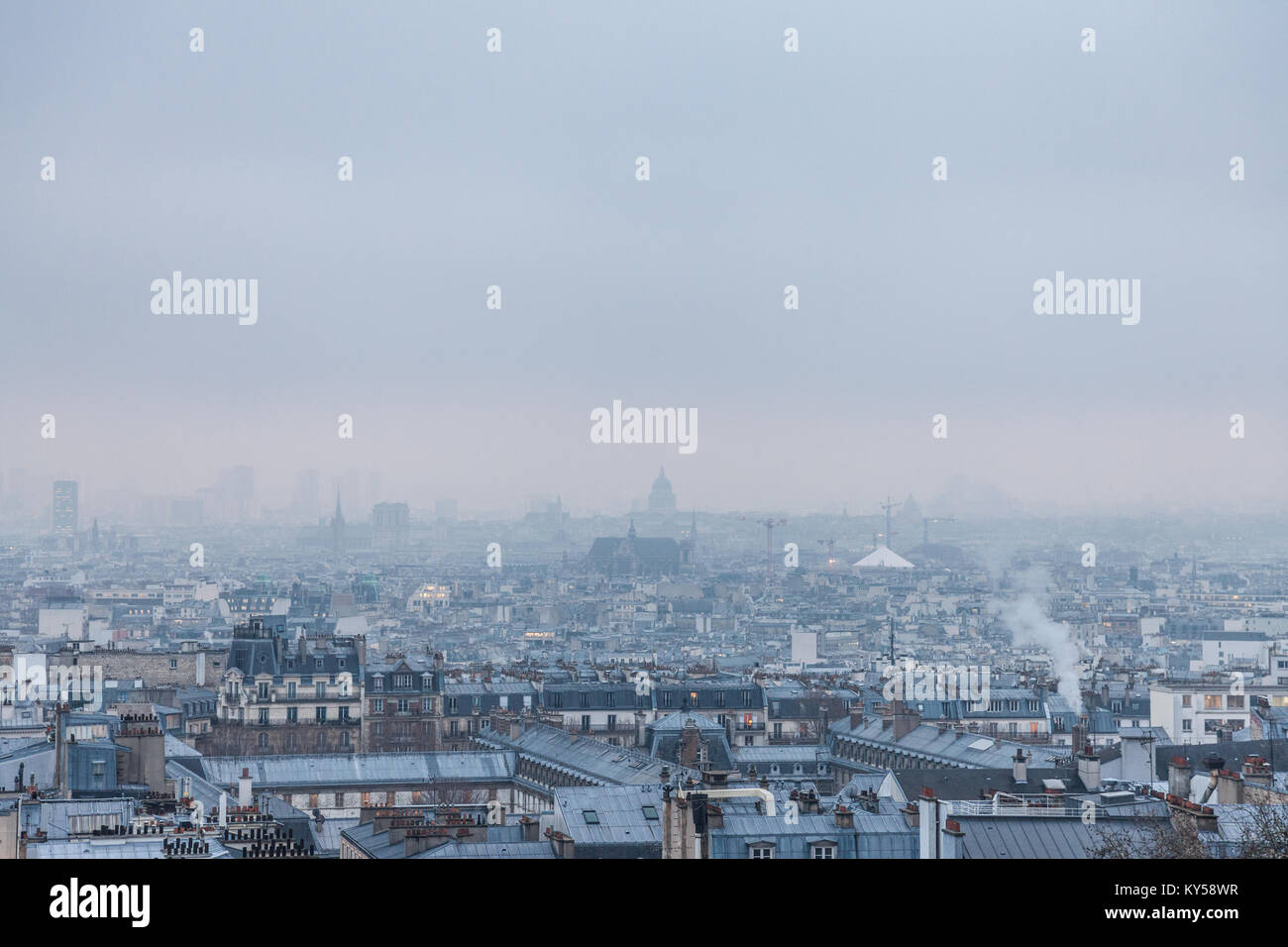 Aerial view of Paris, capital city of France, during a cold winter afternoon, with clouds and fog generated by pollution. - Stock Image