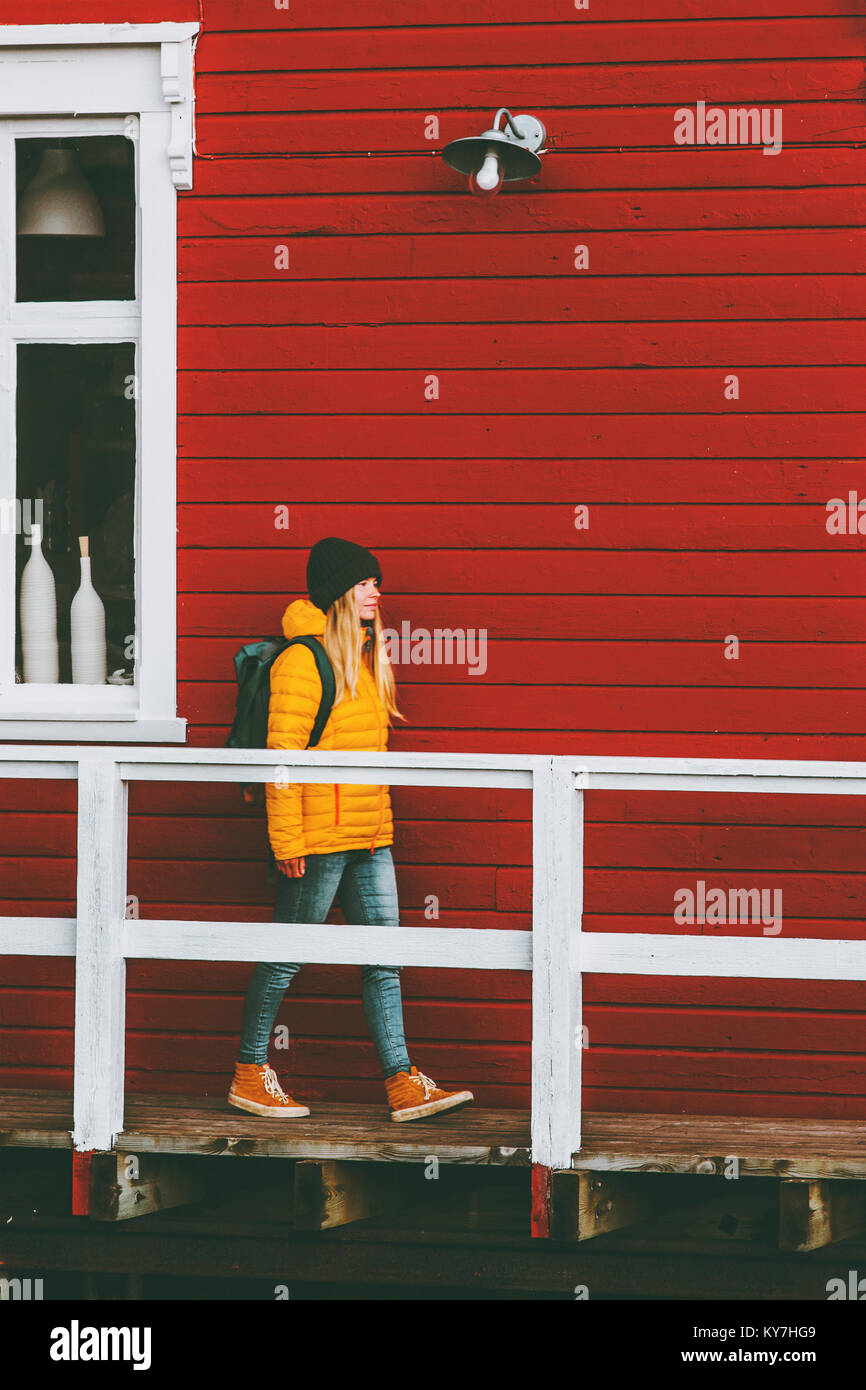 Traveler woman walking in Norway village red house wall on background Travel Lifestyle concept winter vacations - Stock Image