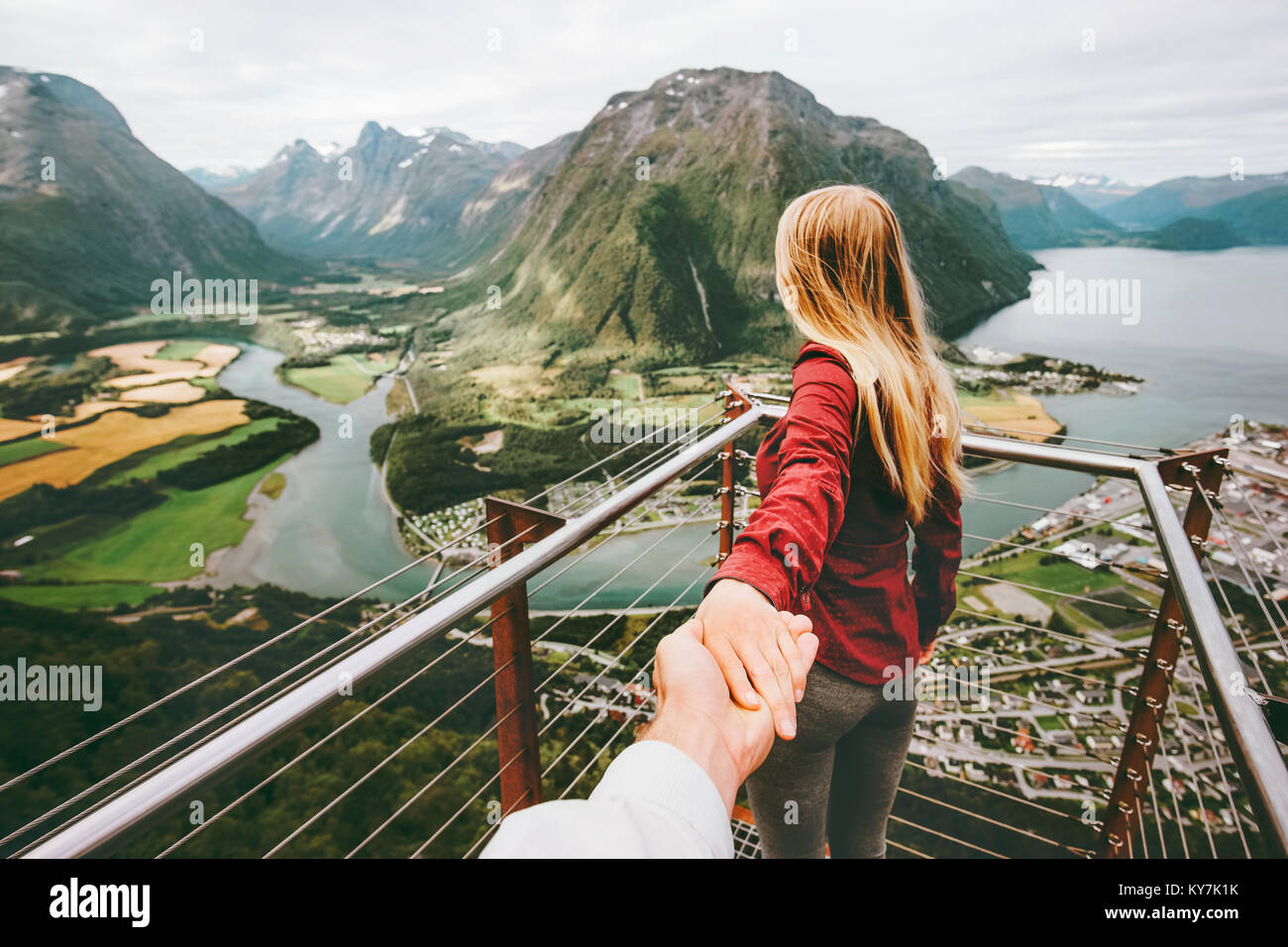 Couple Man and Woman follow holding hands in Norway mountains Love and Travel happy emotions Lifestyle concept. - Stock Image